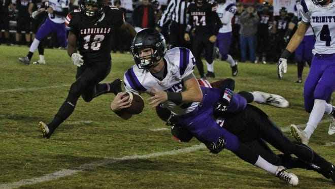 Trinity's Eli Parker reaches out for a gain Friday against Adamsville.