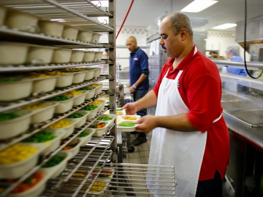 Tri-County Office on Aging Meals on Wheels employee Salah Ahmed, right, and Willie Jones, work a food sealer and conveyer belt to ensure food is delivered fresh and ready-to-eat, Friday, March 24, 2017, in the kitchen at the Lansing Meals on Wheels headquarters on Lansing's south side.