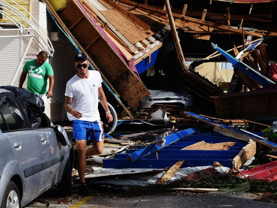 Hurricane Irma pummeled St. Maarten/St. Martin and other northern Caribbean islands Wednesday as it tore a disastrous path through the Atlantic toward the continental U.S. Here, these men climb through debris in Pelican Key, a wealthy area with condos and resorts.