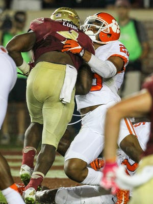 Florida State running back Dalvin Cook (4) runs through Clemson safety Van Smith (23) to score during the second quarter on Saturday at Doak Campbell Stadium in Tallahassee, Florida.