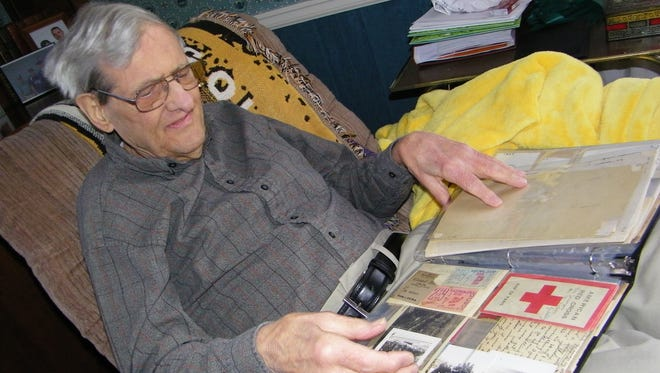 John McConnell looks over a photo album with keepsakes of his time as a glider pilot during World War II.