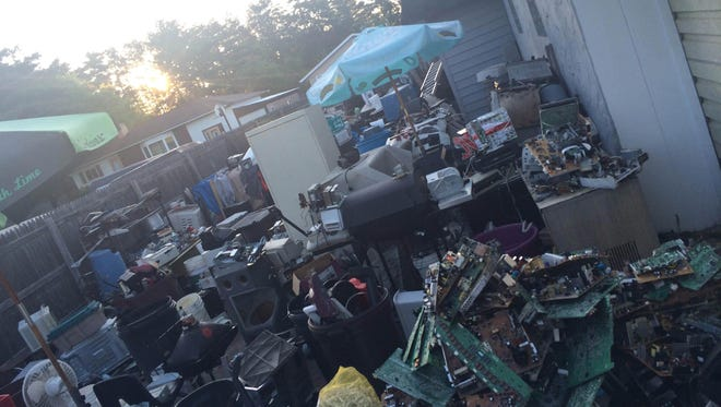 David Roth's collection behind the privacy fence of his Schofield Avenue residence as seen in a June 2, 2015, photo taken by Weston village staff. Officials have contacted the state Department of Natural Resources out of concern that hazardous materials are seeping from Roth's electronic items.