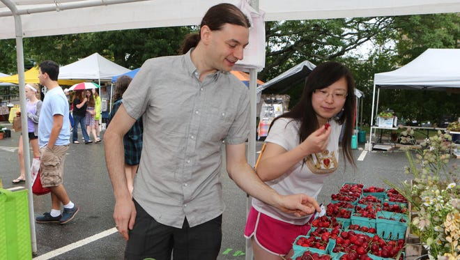 Mike Zollner and his wife Peilin Zollner from Port Chester shop for cherries at the Mead Orchards booth at the Pleasantville Farmer's Market, June 20, 2015. In the summertime, he buys about 85% of his food items at various farmer's markets in the region.