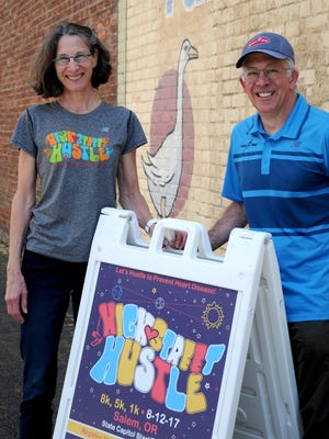 Susan and John Gallagher of Gallagher Fitness Resources show off a sandwich board advertising the High Street Hustle, an 8K run, a 5k run and walk, and a 1k kids walk/run/crawl or otherwise step out event coming up Aug. 12. The deadline to register at a discounted rate is this Saturday night at 11:59 p.m.