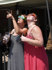 Gerrie Prewitt of Mountain Home (left) and her daughter Jessica Prewitt of Fayetteville watch the solar eclipse Monday at the Donald W. Reynolds Library in Mountain Home.