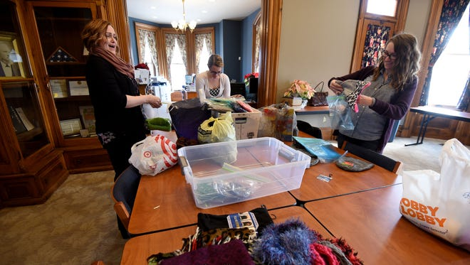 """Nikki Lewis, Stephany Elgin and Emily Volz pack gloves, mittens, hats and scarves in bags at the Chamber of Commerce building on Friday to hang on """"giving trees."""" The bags were later hung from trees outside the Mansfield/Richland County Public Library at Mulberry and Third Streets for people who need them."""