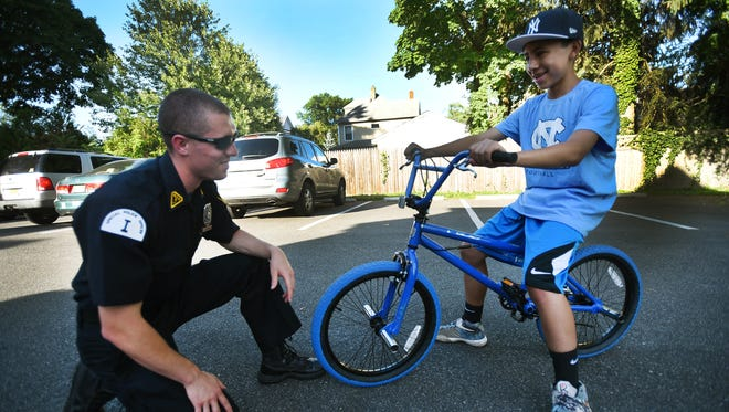 Westwood Special Police Office Ryan Sestanovich, who replaced a young boy's bicycle after it was stolen off his front porch, interacts with the boy Quentin Reilly (age 13) with the new bike at the backyard of Quentin's home in Westwood on 06/25/18.