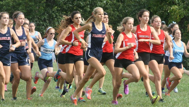 Franklin's Natalie Douglas (navy blue uniform) and members of the Livonia Churchill cross country team (red jerseys) established themselves early in Wednesday's race.