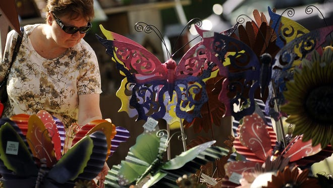 Customers peruse the many garden ornaments for sale during the 22nd annual Garden Fair in Washington Park on Saturday, June 9, 2012, in Manitowoc.