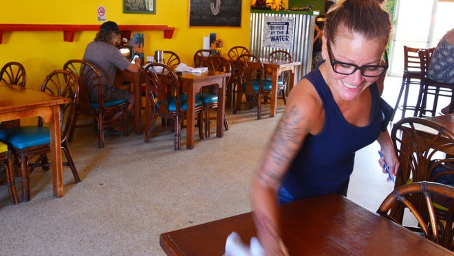 A waitress cleans a table at a restaurant in Cocoa Beach.