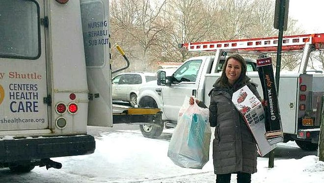 Courtney Bauer, Western New York regional marketing director for Centers Health Care, shows off some of the toys donated for the Fidelis Care toy drive program.