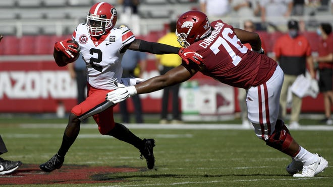 Georgia defensive back Richard LeCounte (2) runs past Arkansas lineman Myron Cunningham (76) as he returns an interception during the first half of an NCAA college football game in Fayetteville, Ark., Saturday, Sept. 26, 2020.