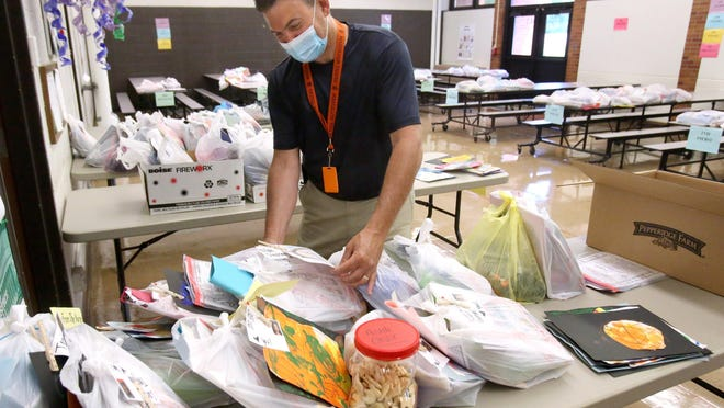 Mike Medure, principal of Franklin Elementary School, looks over bags of student belongings left at the building. Stark County schools are preparing for students to return to class this fall.