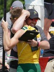 Coach Paul Donart, right, hugs Lucas McCormick following