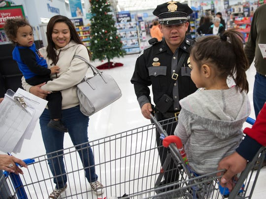 Officer Daniel Jacquez, center, with the New Mexico State Police, asks Aniella Baeza, 4, if she had a good time shopping with him during the Shop with a Cop event Saturday, Dec. 17, 2016 at the Wal-Mart on Valley Drive. Jacquez accompanied Aniella, her brother Giovanny Baeza, their mom Crystal Ortega, left, and their dad Leo Baeza, through the store. Participating families were allotted $100 to spend on clothes and toys.