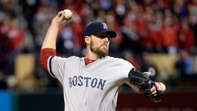 Boston Red Sox pitcher John Lackey throws a pitch against the St. Louis Cardinals in the 8th inning during game four of the MLB baseball World Series at Busch Stadium.