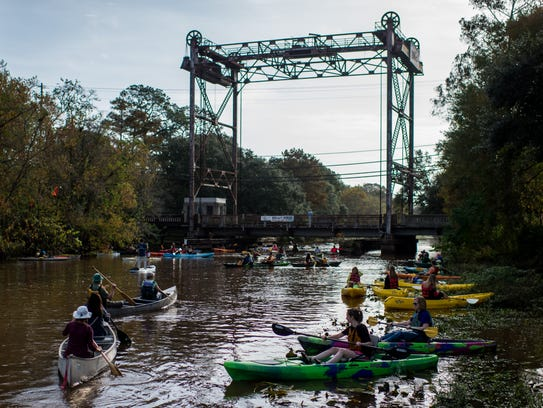 Boaters paddle their canoes and kayaks on the Bayou