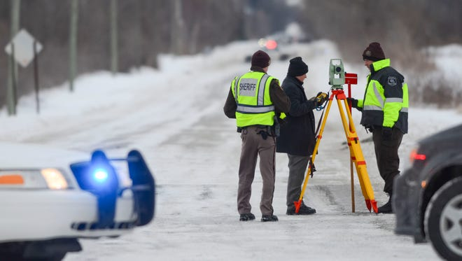Officers from the St. Clair County Sheriff's Department investigate a scene where bags of human remains were discovered Jan. 30, 2014, in St. Clair Township, Mich.