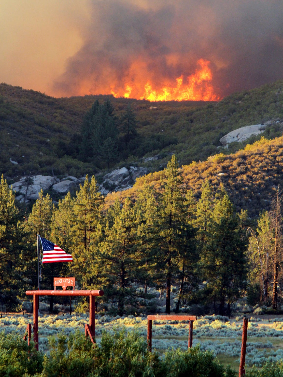 The Mountain Fire burns over a ridgeline behind the Garner Cattle Co. near the Southern California mountain communities of Idyllwild, Mountain Center and Garner Valley on July 15, 2013.