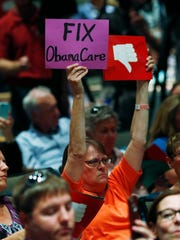 A constituent holds up signs calling for repair of the Affordable Care Act as U.S. Rep. Mike Coffman, R-Colo., speaks during a town hall meeting in a hall on the campus of the University of Colorado Medical School late Wednesday, April 12, 2017, in Aurora, Colo. Town halls have become a risky proposition for GOP members of Congress since the election of President Donald Trump. (AP Photo/David Zalubowski)