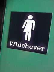A gender-neutral sign is posted outside bathrooms at Oval Park Grill on May 11, 2016, in Durham, N.C. In 2016, North Carolina passed a bathroom bill that restricted protections for LGBT individuals and saw significant economic losses reaching $3.76 billion over a 12-year period, according to an Associated Press analysis. The bill has since been partially repealed.