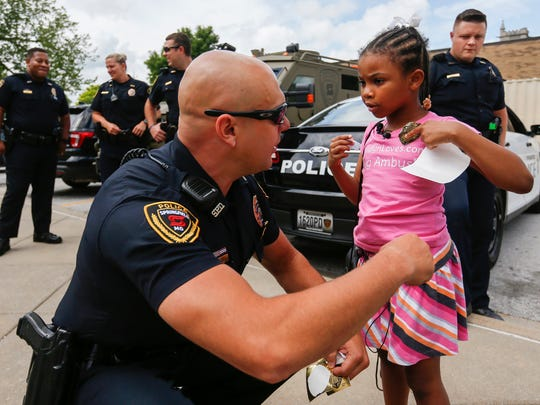 Rosalyn Baldwin, 7, gets help from officer Eric Hawkins putting on a police badge sticker during her visit to the Springfield Police Department on Monday, June 5, 2017. Rosalyn is traveling with members of her family to hug police officers in all 50 states.