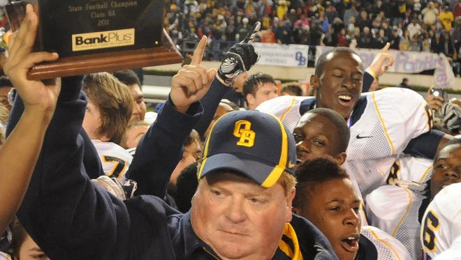 Olive Branch head coach Scott Samsel raises the trophy after defeating Petal 35-34 during the 6A state title game in 2011.