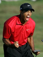 Tiger Woods reacts after sinking a birdie putt on the