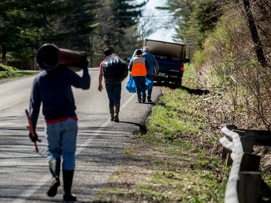 Members of Port Huron Boy Scout Troop 168 carry bags of garbage to a vehicle as part of an annual spring cleanup Saturday, April 23, 2016 on Abbottsford Road in Clyde Township.