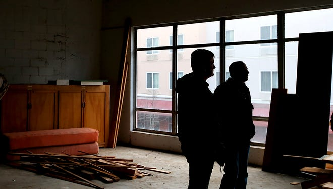 Sound West Group's Wes Larson and Mike Brown are silhouetted Friday against the windows inside of the second story of the Weir building, which they are renovating into apartments, in downtown Bremerton.