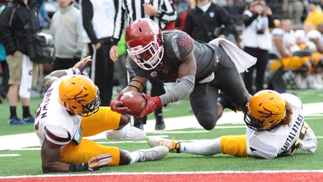 Washington State Cougars running back Jamal Morrow (25) dives for a touchdown against Arizona State Sun Devils defensive back Kweishi Brown (10) and defensive back Dasmond Tautalatasi (30) during the second half at Martin Stadium. The Cougars won 38-24.