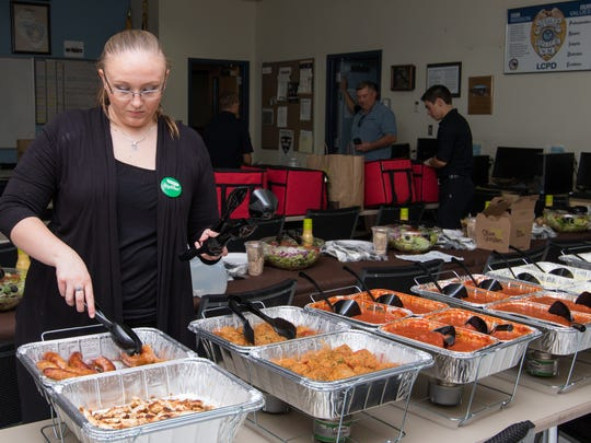Olive Garden employee Amber Auge sets up the luncheon buffet provided Monday for the Las Cruces Police Department on Labor Day.
