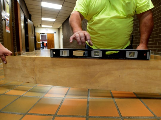 A level is used to demonstrate how uneven one of the hallway floors is at North Middle School.