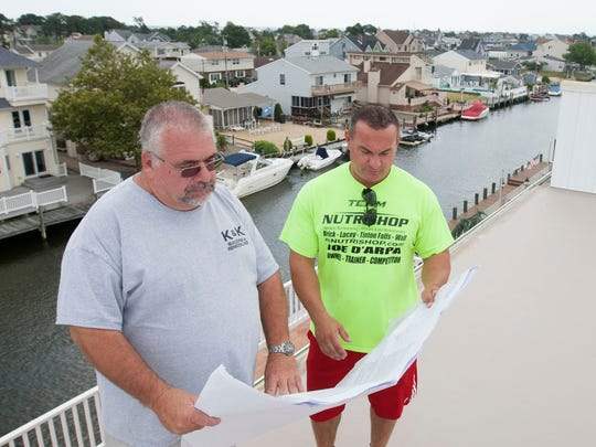 John Kelly, left, owner of K&K Building and Remodeling, and Joe D'Arpa look over the plans for D'Arpa's new home still under construction in Toms River, N.J.