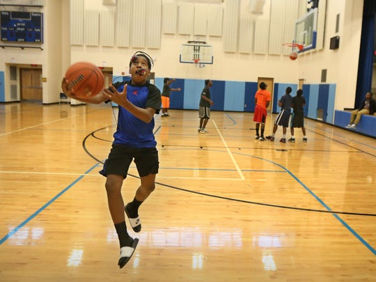 Zeaquan Walker, 12, of Rochester loses his headphones but not his concentration as he practices his layups during the after-school hours in the gymnasium at School 17 on Orchard Street in Rochester on Oct. 19, 2015.