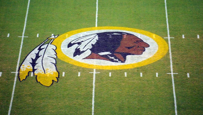The Washington Redskins logo is displayed at midfield before the start of a preseason NFL football game in Landover, Md. The team's nickname, which some consider a derogatory term for Native Americans, has faced a barrage of criticism.
