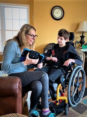 Danielle Karcz, who serves as president of the One Sky Family Support Council,  works with her 12-year-old son Peyton on his remote learning.