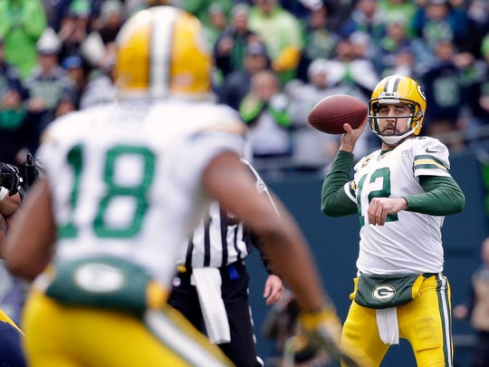Green Bay Packers quarterback Aaron Rodgers (12) looks to pass to Randall Cobb (18) during the first half of the NFL football NFC Championship game against the Seattle Seahawks.