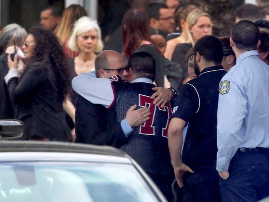 Mourners console each other during the funeral service for Marjory Stoneman Douglas High School assistant football coach, Aaron Feis. at the Church by the Glades in Coral Springs, Fla. Football players wearing Stoneman Douglas jerseys carried Feis' casket into the service at the church where family and friends gathered to remember him as loyal and caring.