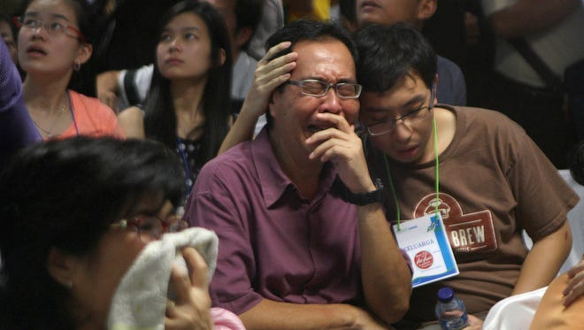 Relatives of passengers on the missing AirAsia jet react after seeing a television broadcast announcing the discovery of bodies and debris at the crisis center at Juanda International Airport in Surabaya, Indonesia.
