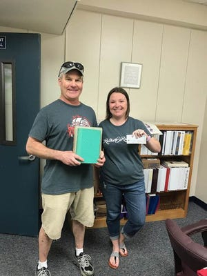 David Harvey (left), who attended Cullen Middle School in the early 1970s, returned two long overdue books to Cullen librarian Morgan Davis last month.