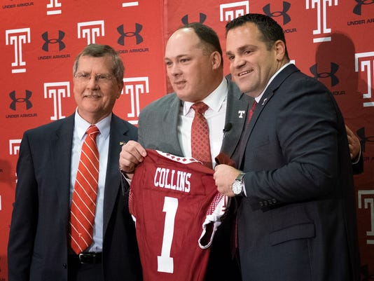 FILE - In this Dec. 14, 2016, file photo, Geoff Collins, center, stands between Temple University president Richard Englert, left, and athletic director Pat Kraft, during an NCAA college football news conference in Philadelphia, where Collins was introduced as Temple's new head football coach. Collins, former Florida defensive coordinator, has brought swag and Nick Saban structure to Temple. (Ed Hille/The Philadelphia Inquirer via AP)