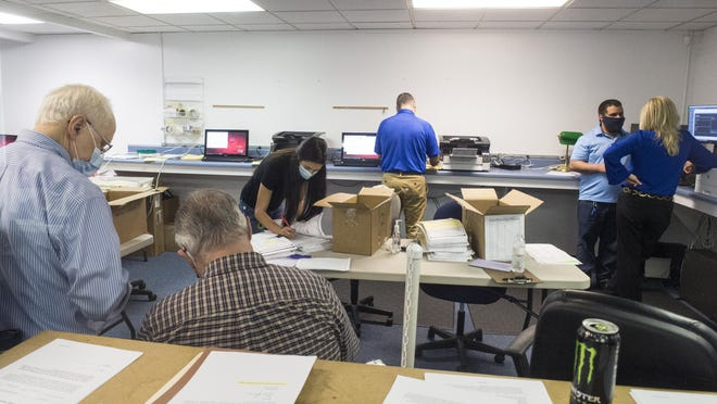 Republican observers, left, watch as election officials count absentee ballots during the Georgia presidential election recount at a Richmond County elections facility in south Augusta, Ga., Monday morning November 30, 2020.