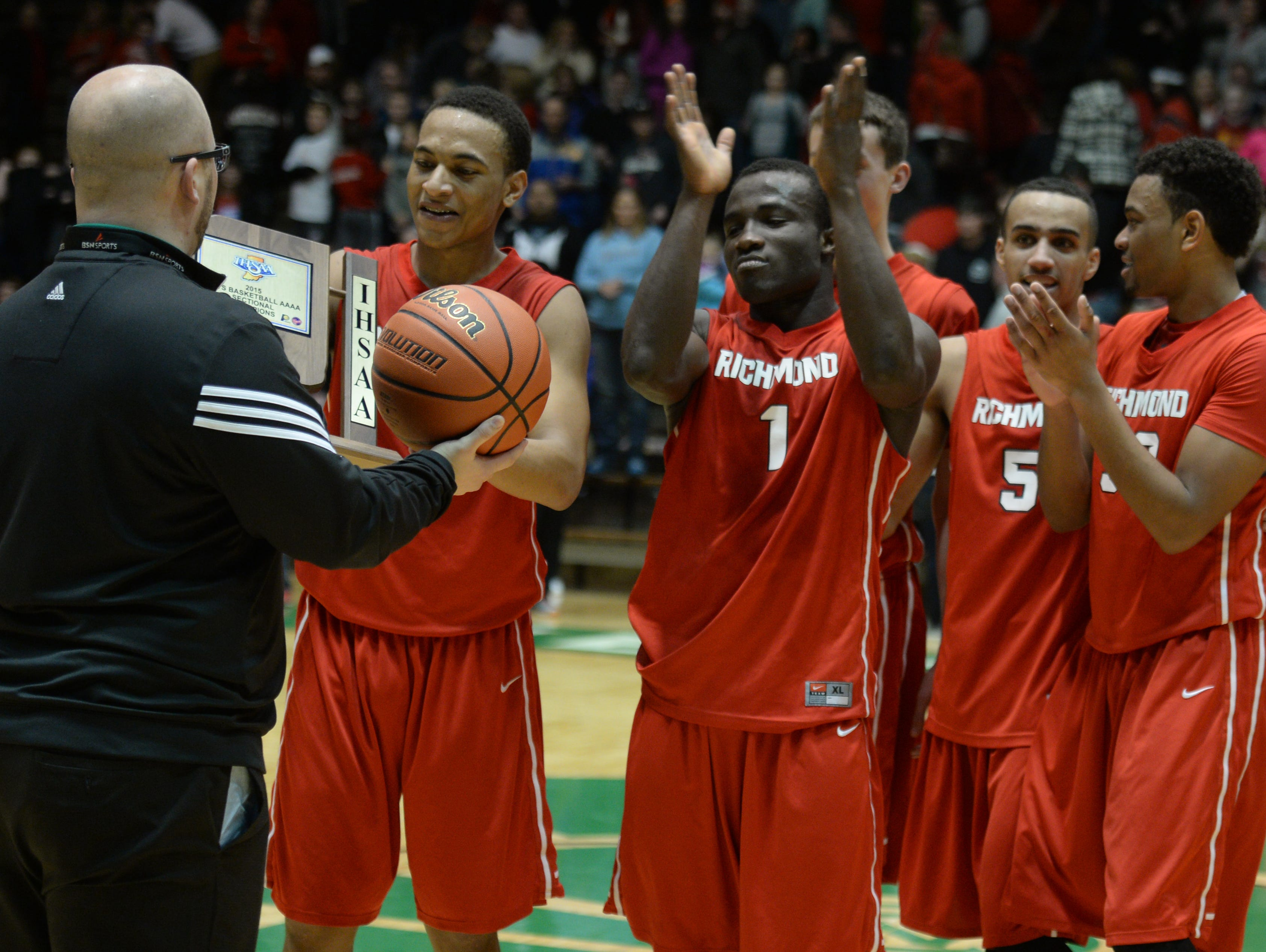 New Castle High School athletic director Brandon Ecker presents a game ball and sectional championship trophy to Richmond's Davious Webster, Joel OKafor, Bryce Austin, Isaiah Rader, Auntonio Brown and Tre Sanders after the Class 4A sectional basketball championship game March 7 in New Castle.