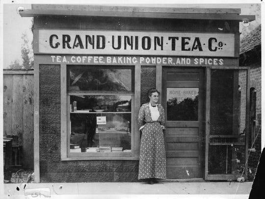 Mrs. Fannie Paxton stands in front of her Farmington business, the Grand Union Tea Co., in 1907.