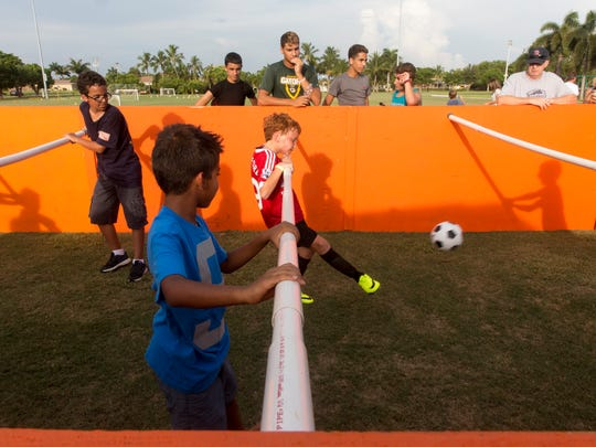 Ivan Harrison, 10, center, of Naples, kicks the ball as part of a human foosball game during the Hot Summer Nights event in Mackle Park on Marco Island in July.