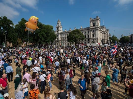 Demonstrators raise a effigy of Donald Trump, being