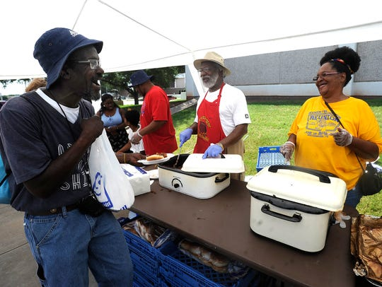 Etta Wilson (right) laughs as she hands out barbecue