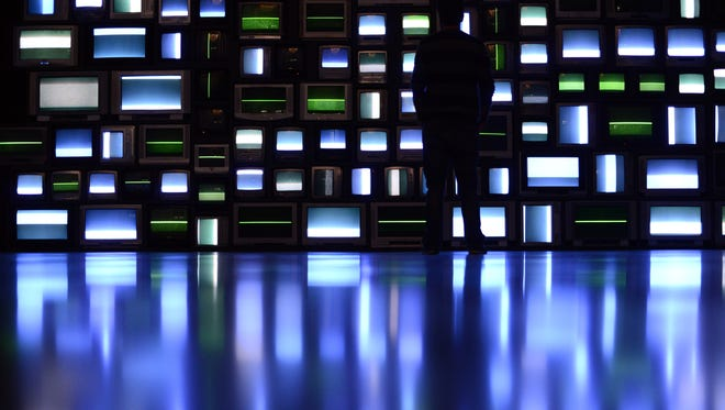 FILE - in this visitors look at a video installation, comprising of 106 TV sets, by American artist Susan Hiller in the Abattoirs Museum in Toulouse, southern France, as part of Toulouse's International Art Festival, on June 1, 2014.