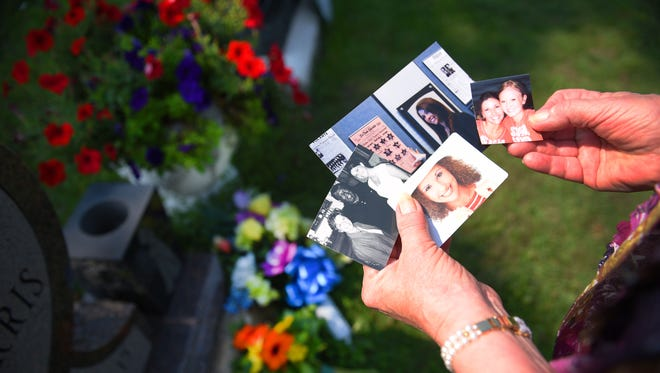 Janine Harris holds out photos of her daughter Nicole Vallie Harris Saturday at Nikki's grave at Mount Pleasant Cemetery. The photos are of Nikki and her stepdad Mike Harris, her and her best friend and a senior photo.